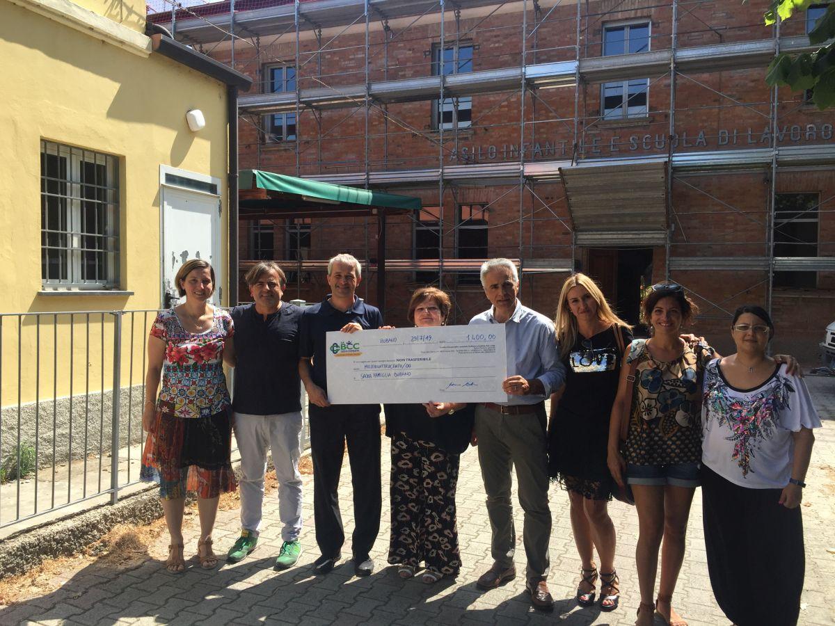 Don Antonio, a sinistra, la direttrice Carmen Falconi e Maurizio Martini de LA BCC, con l'assegno